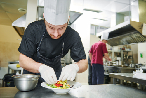 Chef Using White Gloves to Garnish a Dish