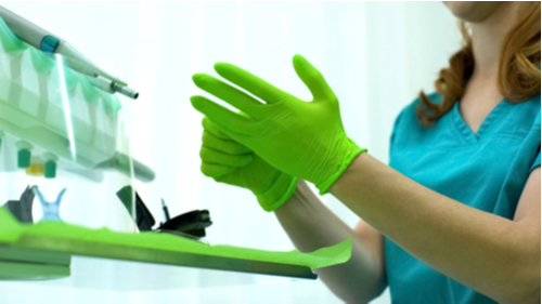 Medical Professional Wearing Green Disposable Gloves